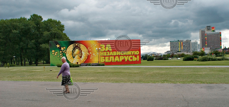 A woman walks past a billboard that reads: For an Independent Belarus.
