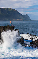 A woman standing on rocks contemplates the ocean while waves break around her, Hanalei Bay, Kaua'i.