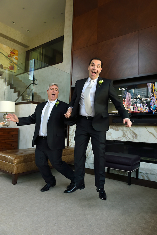 The two grooms jumping for joy.