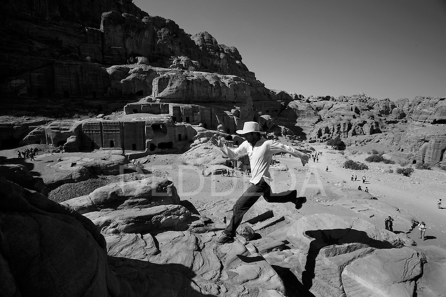 A male tourist in a hat jumps across a gap in the stone cliffs in the Nabatean ancient city of Petra, Jordan.