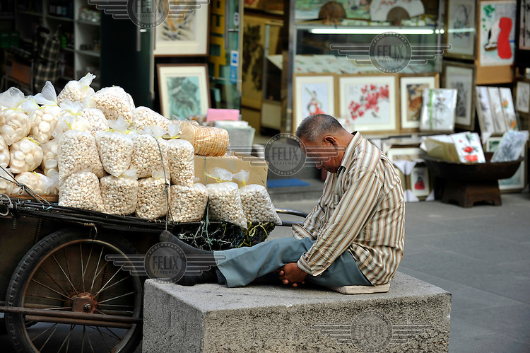 A snack vendor sleeps in the popular arts and dining district of Insadong.
