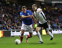 Kal Naismith pressured by Kevin Holt in the Rangers v Queen of the South Quarter Final match in the Ramsdens Cup played at Ibrox Stadium, Glasgow on 18.9.12.