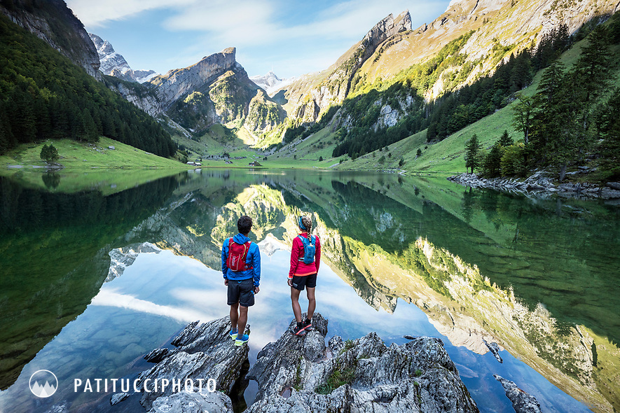 A couple stands on the shore of the Seealpsee, looking at the reflection of the Santis and Alpstein mountains. Switzerland.