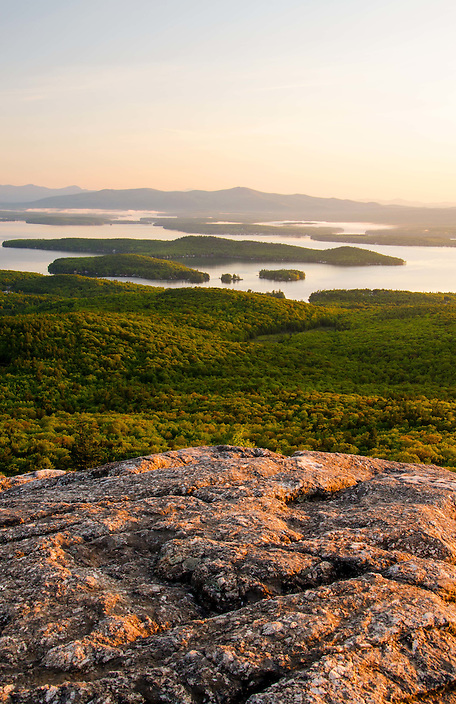 Lake Winnipesaukee wakes up on a foggy morning, seen  from the summit of Mt. Major.