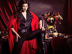 Beautiful fashionably dressed young woman wearing black with red coat posing in front of festive table filled with food and wine