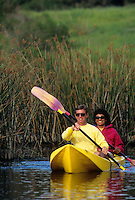 Couple paddling a kayak on a lake.