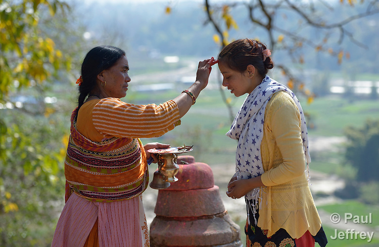 Puneshewri Shrestha makes a mark, known in Nepal as a tika, on the forehead of Asha Khadka in Sanogoan, Nepal. Shrestha leads Hindu religious practice in the Newar community, which was hard hit by the April 2015 earthquake that ravaged Nepal. <br /> <br /> Most residents here lost their homes in the quake. Yet the ACT Alliance has provided a variety of services here since the quake, including blankets, tents, and livelihood assistance, and is helping villagers form the tens of thousands of cement blocks they will need to construct permanent housing.