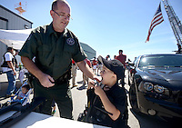 NWA Democrat-Gazette/BEN GOFF @NWABENGOFF<br /> Rick Keyes, a detective withe the Benton County Sheriff's Office, helps Gray Perrin, 5, of Bella Vista try on a SWAT bullet-resistant vest on Saturday Sept. 12, 2015 during the Sheep Dog Impact Assistance annual Patriot Day event at Bentonville Municipal Airport. The event honored the victims of the Sept. 11, 2001 terrorist attacks and offered visitors a chance to get an up close look at military and emergency response vehicles.