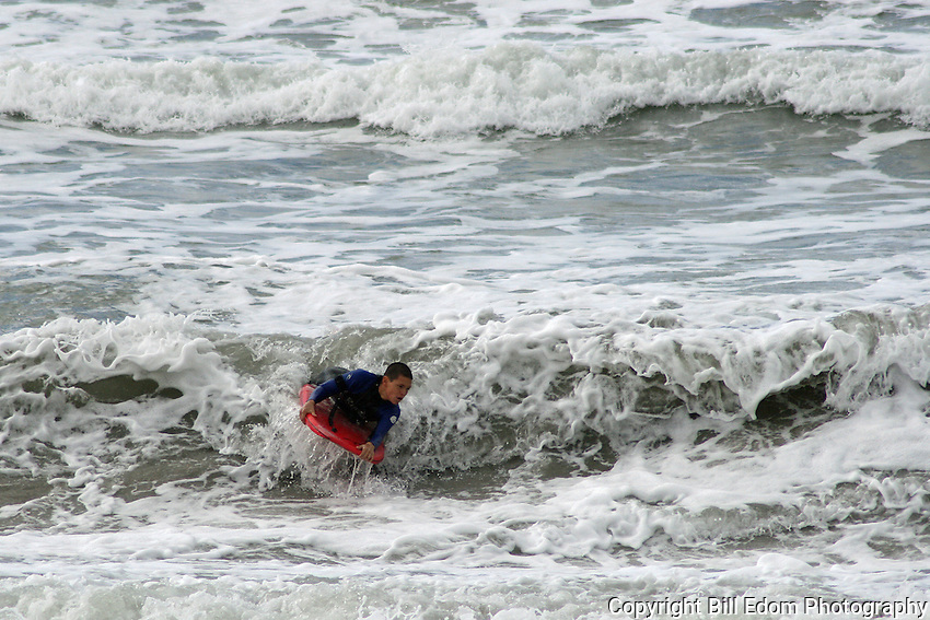 A Body Boarder skims across the rough water at an Oceanside, CA Beach.
