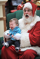 STAFF PHOTO ANDY SHUPE - Santa Claus reacts Monday, Dec. 22, 2014, as Jacob Parker, 8 months, of Fayetteville cries while sitting on his lap as his photograph  is made in center court of the Northwest Arkansas Mall in Fayetteville. Santa is available for photographs today from 11 a.m. to 8 p.m. and Christmas Eve from 11 a.m. to 6 p.m. with a break from 3-4 p.m.