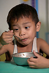 Six-year old Luigi enjoys a meal in the United Methodist Church in the Parola neighborhood of Tondo, a poor section of Maniila, Philippines. Nursing students from the Mary Johnston College of Nursing regularly visit the neighborhood to do health education and monitor the health of residents, at the same time running  a feeding program for neighborhood children.<br /> <br /> The nursing school is supported by United Methodist Women.