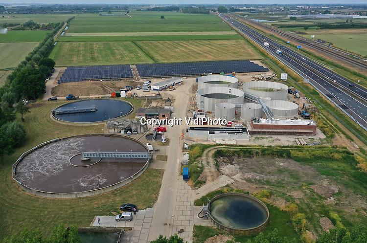 Foto: VidiPhoto<br /> <br /> DODEWAARD – Waterschap Rivierenland verzamelt vanaf volgend jaar zomer de poep en pies van vijf kleinere rioolwaterzuiveringsinstallaties (rwzi) op één centrale plek in de Midden-Betuwe: langs de A15 bij Dodewaard. Op de huidige -nog kleine- rwzi worden op dit moment zes nieuwe bassins bijgebouwd die -inclusief de drie in 1981 gebouwde tanks- regenwater en uitwerpselen van 70.000 inwoners om kunnen zetten in schoon oppervlaktewater. De installatie wordt met de aanleg van 4000 zonnepanelen bovendien energieneutraal. Boeren, telers en tuinders die gebruik maken van het water uit de Linge profiteren in eerste instantie, omdat de waterkwaliteit van de Linge dankzij nieuwe zuiveringstechnieken verbetert. De verwachting is ook dat het riviertje aantrekkelijker wordt voor vissoorten als forel en mogelijk zelfs zalm. Bouwer van de nieuwe rwzi is Eliquo uit Barneveld. Inclusief aanleg van nieuwe rioolbuizen en de bouw van een energiefabriek bij Tiel kost het totale vernieuwingsproject 50 miljoen euro. Vijf kleinere rwzi's in de regio worden vanaf volgend jaar juli hierdoor overbodig.