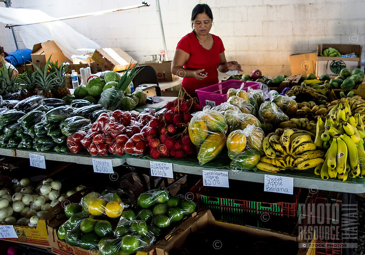 A shopper selectively chooses produce at the Hilo Farmers Market, Big Island of Hawai'i.