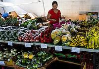 A shopper selectively chooses produce at the Hilo Farmers Market, Big Island of Hawai'i.