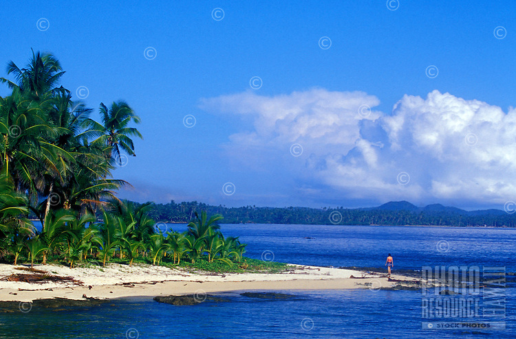 Woman walking alone on white sand beach of palm lined point, Siargao Island, Philippines