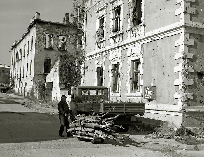 A man pulls a handcart stacked with firewood past buildings riddled with bullet holes in Mostar, Bosnia Herzegovina.<br />