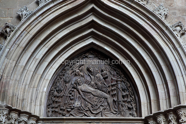 Tympanum with Pieta relief, above Calle de la Piedad, an entrance to the Patio, Barcelona Cathedral, or Catedral de la Santa Creu i Santa Eulalia, (Catedral de la Santa Cruz y Santa Eulalia, Cathedral of the Holy Cross and Saint Eulalia), 13th-15th centuries, with 19th century facade, Barcelona, Catalonia, Spain, also known as la Seu, seat of the Archbishop of Barcelona. St Eulalia, a young martyr, is entombed in the crypt of this Gothic style Cathedral. Picture by Manuel Cohen