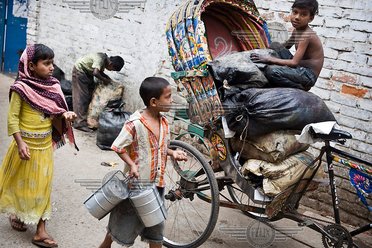Two children, one carrying a couple of tiffin tins, pass two street children collecting rubbish for recycling.