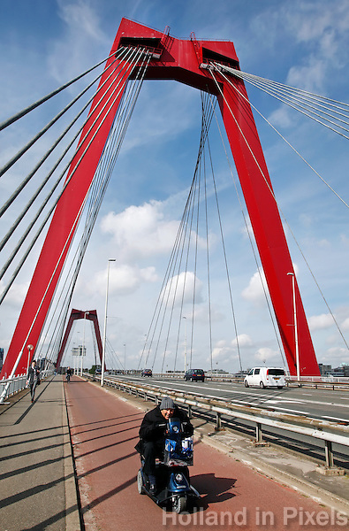 Lachende man op een scootmobiel op de Willemsbrug in Rotterdam