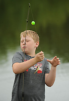 NWA Democrat-Gazette/ANDY SHUPE<br /> Brooks Williams, 9, of Elkins gets splashed in the face Thursday, June 15, 2017, by a small fish that he caught in Carter Pond during the annual Elkins Public Library Fishing Derby in Elkins. Prizes were awarded in several categories for children 16 and under before lunch was served.