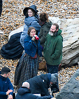 BNPS.co.uk (01202 558833)<br /> Pic: Graham Hunt/BNPS<br /> <br /> Kate Winslet and Saoirse Ronan with director Francis Lee during a break in filming on the Beach at Eype near Bridport in Dorset yesterday for the new film Ammonite about the life of fossil hunter Mary Anning.