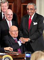 Washington, D.C. - March 23, 2010 -- United States Representative Charlie Rangel (Democrat of New York), right, shakes hands with U.S. Representative John Dingell (Democrat of Michigan), lower left, as U.S. President Barack Obama (not pictured) signs the version of the health care bill that was passed by the U.S. House of Representatives in the East Room of the White House in Washington, D.C. on Tuesday, March 23, 2010.  U.S. Senator Max Baucus (Democrat of Montana), upper left, and U.S. Representative Henry Waxman (Democrat of California), center left, look on. Credit: Ron Sachs/CNP/AdMedia