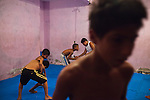 Boys practice mix-martial arts in a program led by a teacher who volunteers his time so that the kids are off the streets at night when there's little to do but find trouble, in Rocinha, the biggest favela in Brazil, with over 100,000 residents, in Rio de Janeiro, Br., on Thursday, Jan. 24, 2013.