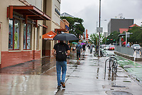 Busy students and pedestrians walking in rain on the UT Drag, Guadalupe Street, next to the University of Texas campus in downtown Austin - Stock Image.