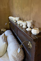 A collection of creamware is displayed on the headboard of an antique double bed