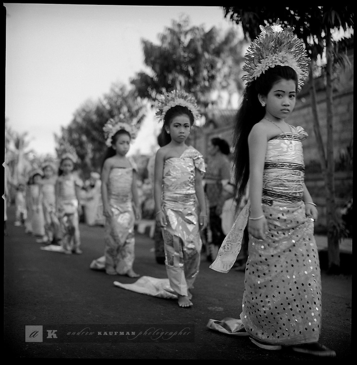 Young balinese girls participate in a Balinese procession that ends with an offering. The girls are wearing the traditional sarong and have flowers in their hair.