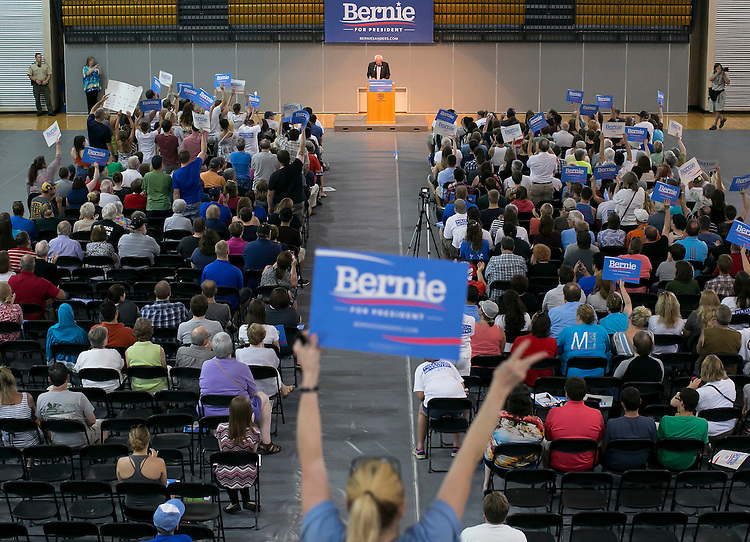 """UNITED STATES - August 16: Supporters cheer and waive campaign posters as Sen. Bernie Sanders, D-Vt., speaks at the Loras College Athletic and Wellness Center in Dubuque, Iowa, on Sunday, August 16, 2015. The """"town meeting,"""" was the fourth campaign event of the day for Sanders. (Photo By Al Drago/CQ Roll Call)"""