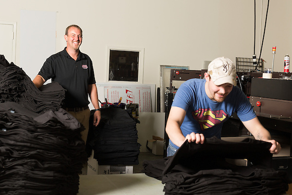 September 18, 2014. Raleigh, North Carolina.<br />  Chuck Sawyer's stores screen print 1000's of t-shirts a week when busy. Here he poses for a portrait in the production part of his main store, while employee Bobby Ward takes newly screened shirts out of the dryer.<br />  Chuck Sawyer, 37, is the owner of three Instant Imprints franchises, specializing in promotional materials such as t-shirts,signs and mugs. Sawyer wishes he had more saved for retirement and is encouraging his none employees to start thinking about how they will save for when they get older.<br /> Publication: AARP Bulletin<br /> Editor: Jenna Isaacson-Fuller<br /> Model Released<br /> Portrait