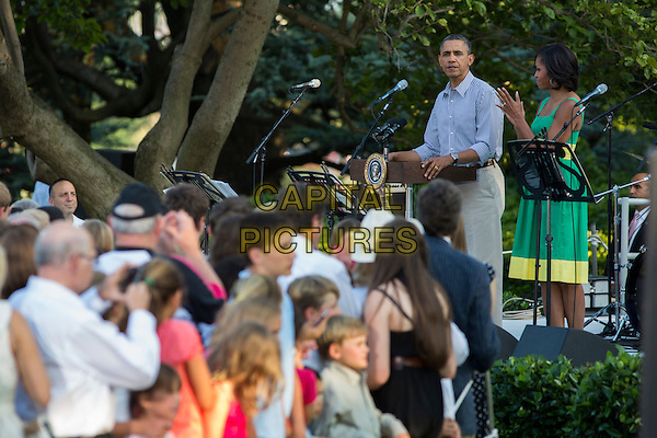 United States President Barack Obama, joined by First Lady Michelle Obama, delivers remarks on the South Lawn of the White House during an annual picnic held for members of Congress in Washington, D.C. on Wednesday, June 27, 2012.  .half length blue shirt green dress podium speech crowd audience married husband wife .CAP/ADM/CNP/KT.©Kristoffer Tripplaar/Pool/CNP/AdMedia/Capital Pictures.