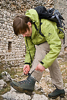 Female hiker tying boots
