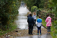 Pictured: A young family look on one of the flooded roads off Dulais Fach Road (B4434) between the areas of Aberdulais and Tonna in Neath, south Wales, UK. Saturday 13 October 2018<br /> Re: Flooding caused by Storm Callum in the Neath area, south Wales, UK.