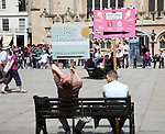Men holding advertising boards sit on bench in the Abbey churchyard, Bath, England