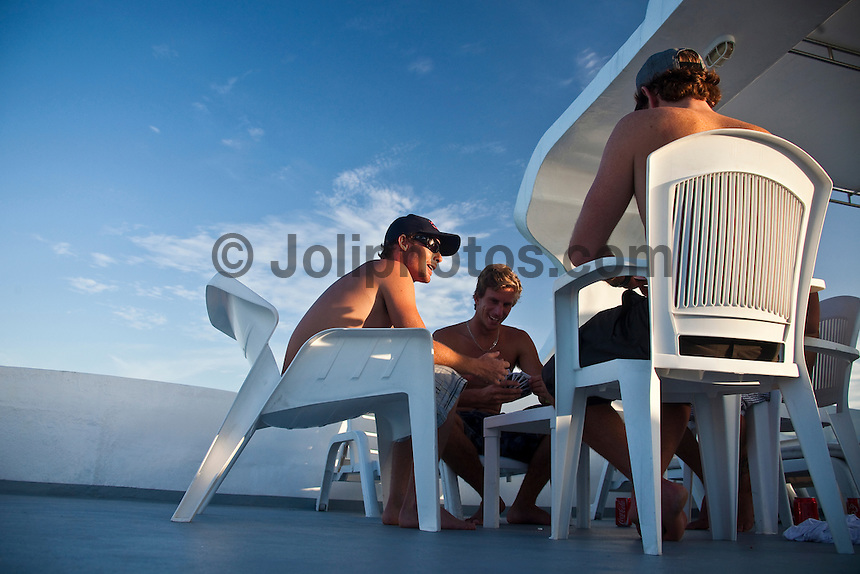 DAN REDMAN (ZAF), ROYDEN BRYSON (ZAF), BRANDON JACKSON (ZAF)  and WARWICK WRIGHT (ZAF) enjoy a card game aboard the Vaagali MV in the Maldives (Monday, June 8th, 2009). Photo: joliphotos.com