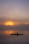 Sunrise on Lake Cassidy with Mount Pilchuck in fog early morning light illuminating a kayaker on a tranquil lake with reflections east of Marysville, Washington State USA