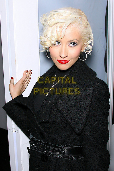 CHRISTINA AGUILERA.Mercedes-Benz Fall 2006 L.A. Fashion Week - Agent Provocateur - DAY 2 held at Smashbox Studios, Culver City, California, USA.Macrh 20th, 2006.Photo: Zach Lipp/AdMedia/Capital Pictures.Ref: ZL/ADM.half length black coat belt red lipstick.www.capitalpictures.com.sales@capitalpictures.com.© Capital Pictures.