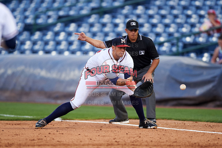 Mississippi Braves first baseman Seth Loman (22) fields a ground ball as umpire Jose Esteras signals fair ball during a game against the Pensacola Blue Wahoos on May 27, 2015 at Trustmark Park in Pearl, Mississippi.  Pensacola defeated Mississippi 7-5 in fourteen innings.  (Mike Janes/Four Seam Images)
