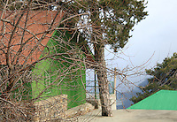 An old fashioned house at a cliff on Troodos mountains,Cyprus,with branches of dry trees hanging on the foreground.