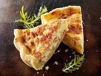 Slices of quiche Loraine on a dark wood background