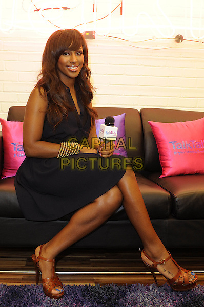Alexandra Burke.TalkTalk Bright Stage - press launch held at Broadwick Street, London, England..August 15th, 2011.full length black navy blue dress sleeveless sitting legs crossed microphone brown sandals.CAP/FIN.©Steve Finn/Capital Pictures.
