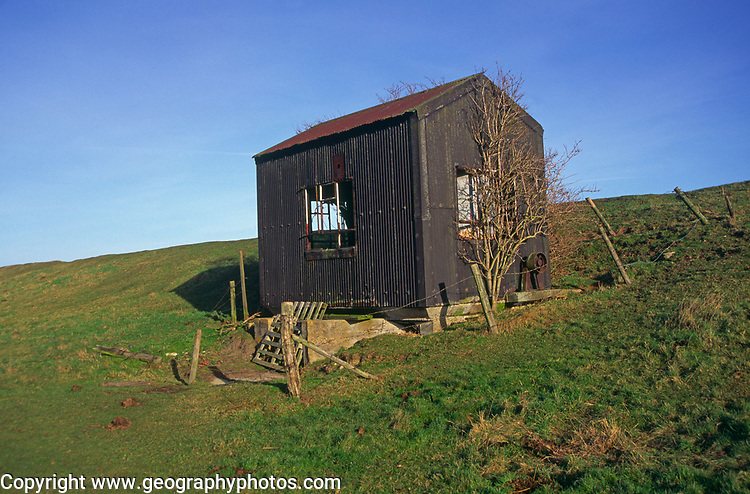 A082P3 Old abandoned corrugated pump house on sea wall dyke East Anglia England Butley Suffolk