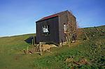 A082P3 Old abandoned corrugated pump house on sea wall dyke East Anglia England Butley Suffolk