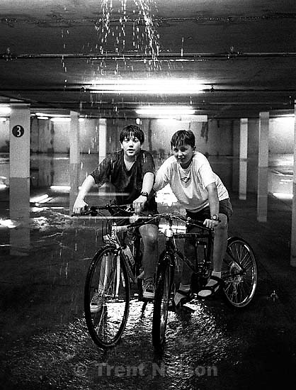 Kids on bikes under flood in parking lot.<br />