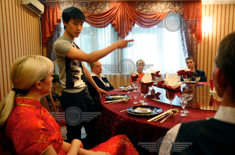 Chinese youngster Qi (surname) Ke hangs gives weekly instructions to waiters and waitresses working at his restaurant on the bank of Amur River in Khabarovsk city in Russia. Amur is part of the border that separates China from Russia.