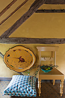 Displayed on the bedroom wall is a yellow antique tray beside a wooden painted chair