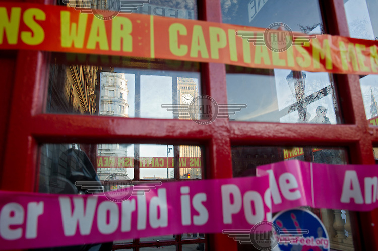 A phone box in Parliament Square, London is wrapped in tape bearing anti-capitalist slogans during a demonstration by students against the government's proposed increase in university tuition fees.