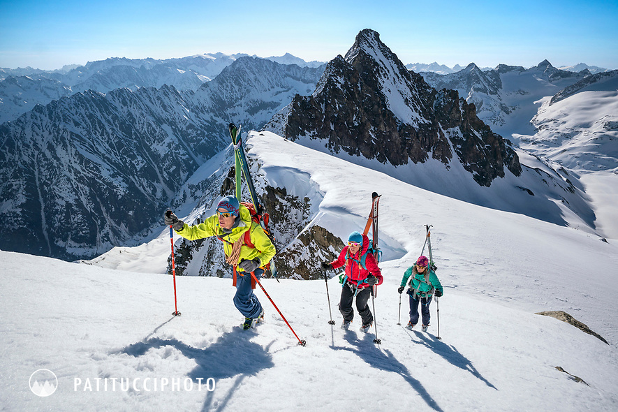 Three skiers with their skis on their packs crampon up the last steep section of the Ränfenhorn before making the huge descent of the Rosenlaui Glacier on the last day of the Berner Haute Route, Switzerland
